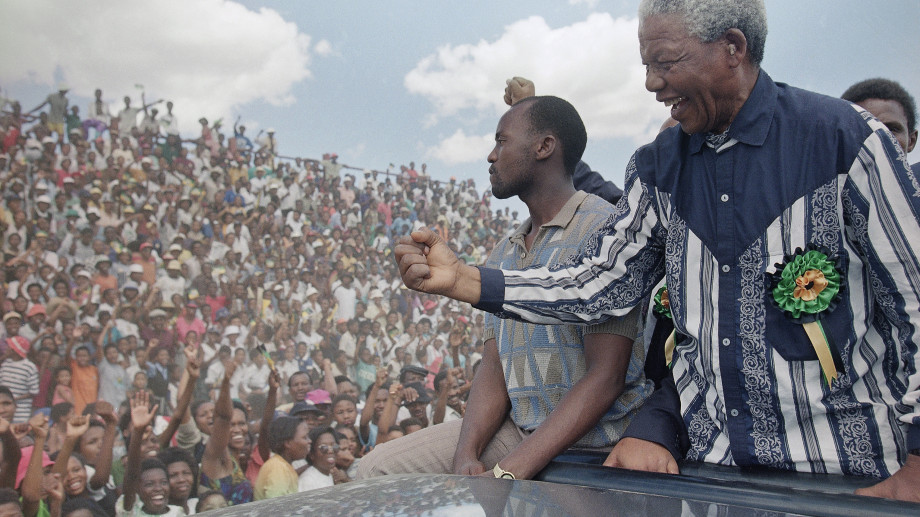 "African National Congress President Nelson Mandela salutes the crowd in Galeshewe Stadium near Kimberley, South Africa, before a ""People's Forum?"" Friday, Feb. 25, 1994. Mandela is on a three-day campaign swing for the April all-race general election through the Northern Cape Province. Mandela called on supporters on Friday to stop chasing President F.W. de Klerk from black areas, saying the ANC could win April?s election ?hands down? without help from hecklers. (AP Photo/David Brauchli)"